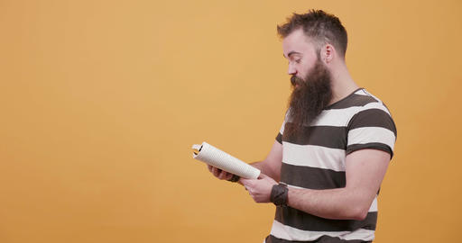 Young handsome bearded man reading a book out loud Live Action