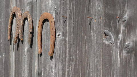 female hands hang rusty horseshoes from wooden country house wall. Closeup. 4K GIF