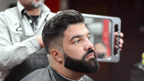 Handsome bearded man looking in the mirror after haircut., at barber shop Footage