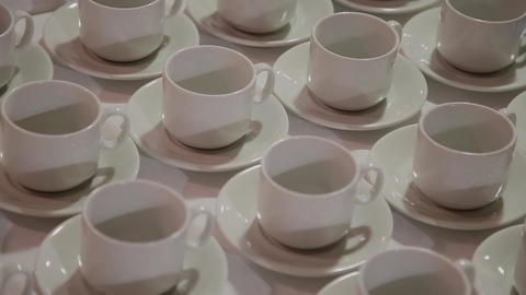 In the restaurant on a table stand white cups and saucers ranked. Many cups Live Action