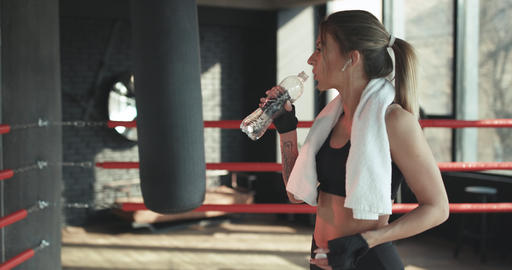 Fitness woman resting taking a break with water bottle drink outside after Footage