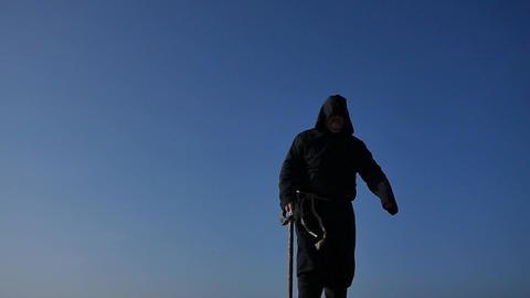old lame man in hoodie uniform slow motion with cane with blue sky background Footage