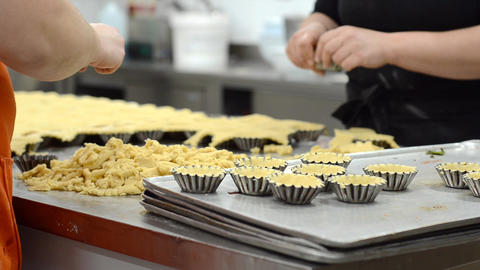 Pastry chef making tartlets, putting the dough in baking dishes, at kitchen of Live Action