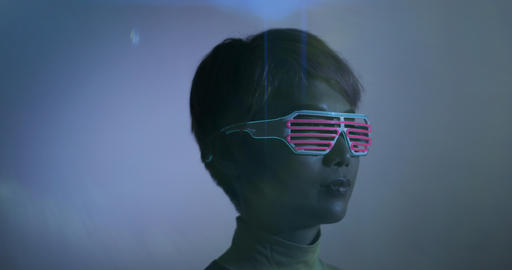 Asian female wearing neon lit glasses in futuristic environment Footage