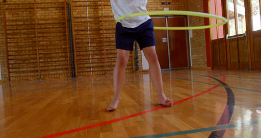 Schoolgirl playing with ring in school gym at elementary school 4k Live Action