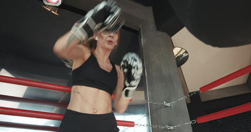 Kickboxing woman training punching bag in fitness studio fierce strength fit Live Action