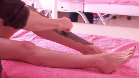 Beautician waxing woman legs, depilation in beauty Spa Live Action