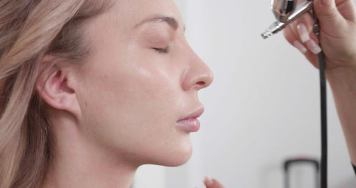 Using airbrush makeup machine to make the face look clean and beautiful Live Action
