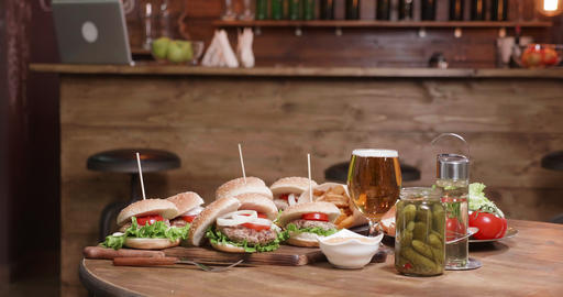A wooden table with burgers on wooden boards in front of a bar Footage