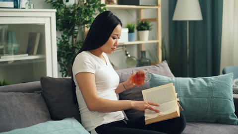 Good-looking Asian woman is reading book enjoying modern literature sitting on Footage