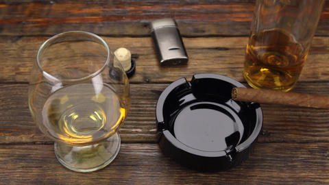 Panorama. A cigar in an ashtray and a glass of alcohol are on the old table Footage