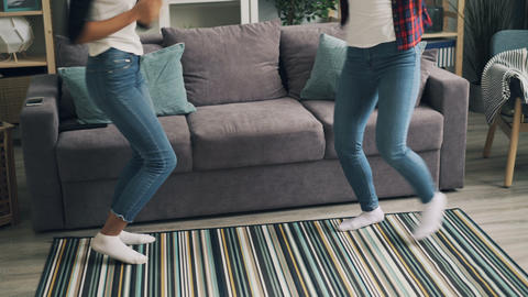 Cute girls in trendy jeans are dancing at home together listening to music and Live Action