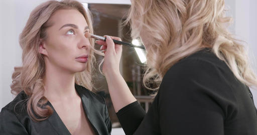 Blonde girl at a beauty salon gets makeup by a professional make up artist Live Action