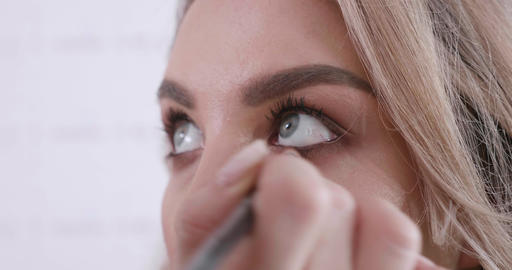 Beautiful young woman with blue eyes made her makeup in a beauty salon Live Action