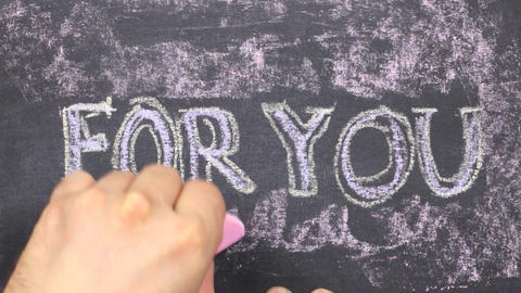 Word FOR YOU is written in chalk on a blackboard. Word circled in chalk Live Action
