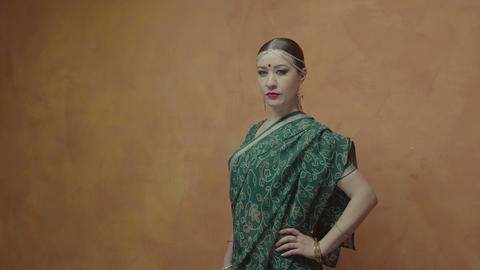 Determined pretty woman in hindu sari posing indoors Live Action
