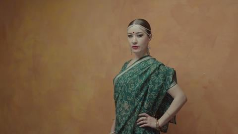 Determined pretty woman in hindu sari posing indoors Footage