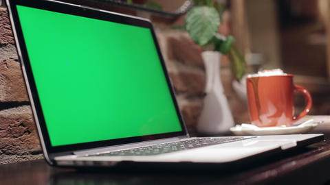 Laptop on wooden table in internet cafe. Green screen and chroma key SLOW MOTION Footage