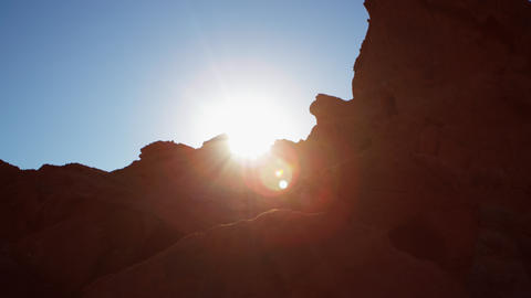 Lens flare shot of sun setting behind rock at Valley of fire stae park Footage
