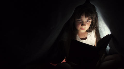 Girl reading book under blanket Footage