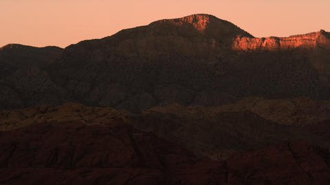 Distant shot of night falling over red mountains Footage