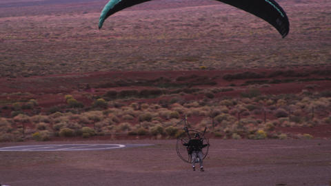 Panning shot of paraglider coming in for landing Footage