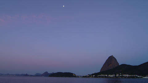 Static shot of Rio's Sugarloaf Mountain in the distance beyond a dark ocean Footage