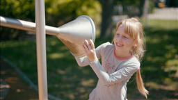 7 year old Cute Blond Girl is Playing with Speaking Tube on Playground in Summer Footage