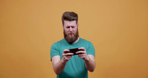 Young attractive man plays an entertaining game on his smartphone Footage