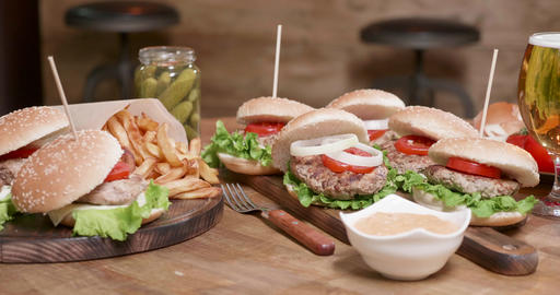 Smooth parallax shot of wide selection of burgers on a wooden round table Live Action