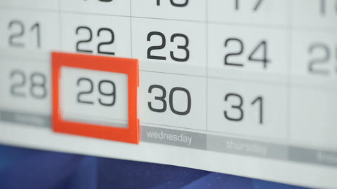 Woman's hand in office changes date at wall calendar. Changes 29 to 30 Live Action