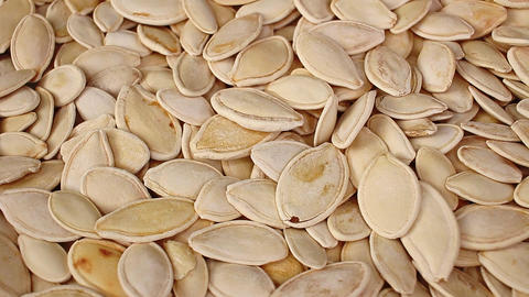 Pumpkin seed seeds closeup texture video on rolling rotating looping plate Live Action