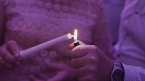 A man lighter lights a candle in the hands of a woman GIF