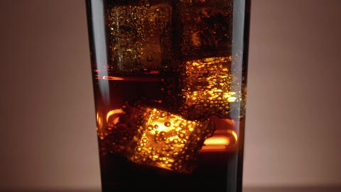 A glass of refreshing Cola with floating ice cubes Live Action