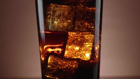 A glass of refreshing Cola with floating ice cubes Footage