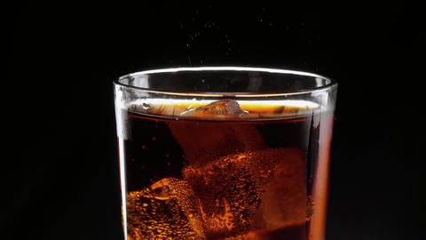 Ice cubes float in a glass of refreshing cola Live Action