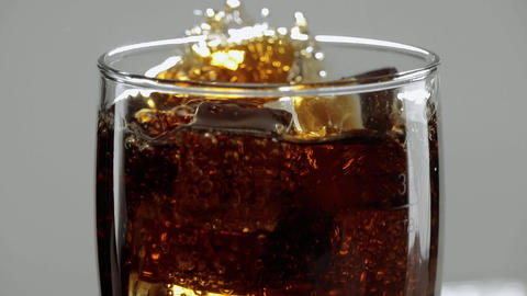 Amazing close up shot of a glas of Cola with ice cubes - refreshing soda in slow Footage