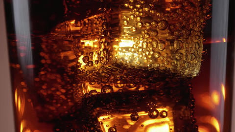 Dancing Ice cubes in a glass of soda - refeshing cold Cola on ice Footage