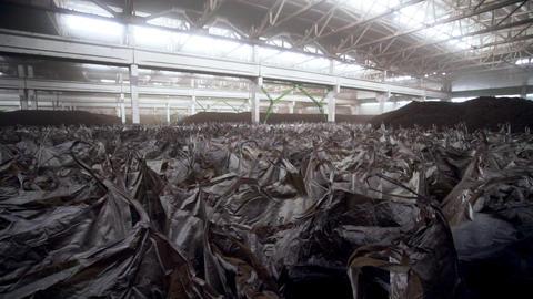 closeup motion along black plastic bags among ore piles Live Action