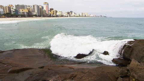 Rocks with white crashing waves and city Footage