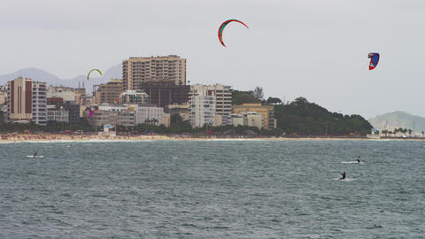 Pan shot of three parasailing surfers with Copacabana city Footage