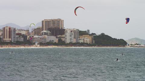 Pan shot of three parasailing surfers with Copacabana city Footage