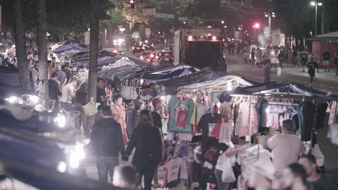 Static shot of tee shirt street vendors crowded along busy street Footage