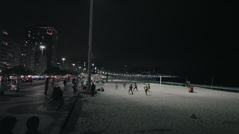 Slow panning shot of volleyball game on beach and street with traffic Footage
