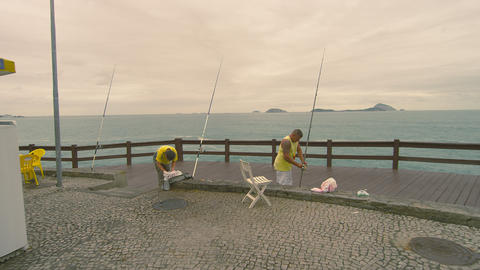 RIO DE JANEIRO, BRAZIL - JUNE 23: Slow dolly shot of men fishing on June 23, 201 Footage