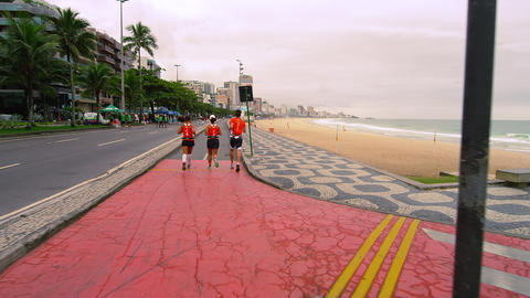 Slow pan of three joggers jogging from a path going towards the road in Rio de J Footage