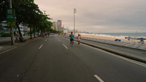 RIO DE JANEIRO, BRAZIL - JUNE 23: Slow dolly shot of couple jogging at Ipanema J Footage