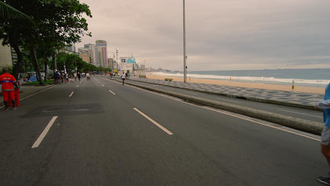 RIO DE JANEIRO, BRAZIL - JUNE 23: Slow dolly shot of joggers, Ipanema Beach on J Footage