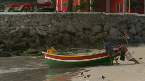 RIO DE JANEIRO, BRAZIL - JUNE 21: Men pushing boat into water on Jun 21, 2013 in Footage