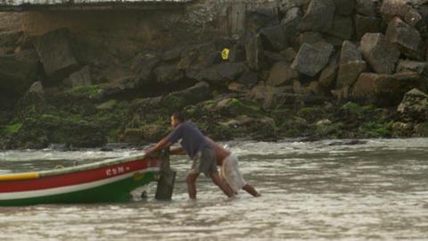 RIO DE JANEIRO, BRAZIL - JUNE 21: Three men pushing boat on water on Jun 21, 201 Footage